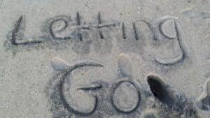 Letting go written in sand